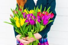 Grand bouquet des tulipes colorées dans des mains de l'enfant Images libres de droits
