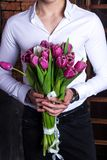 Grand bouquet of tulips, spring flowers in the hands of a sports guy in a white shirt. Festive bouquet for mother`s day. A large bouquet of tulips, spring Stock Image