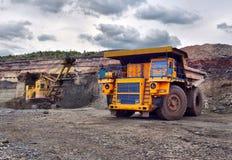 Grand camion à benne basculante de carrière Chargement de la roche dans le déchargeur charge Image libre de droits