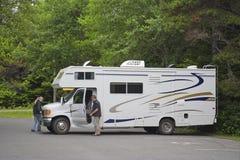Grand camping-car avec des touristes dans les bois photographie stock libre de droits