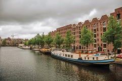 Grand canal bordé d'arbres avec les immeubles de brique modernes, les bateaux amarrés et le ciel nuageux à Amsterdam Images libres de droits