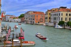 Grand Canal i Venedig, kulöra hus, skeppsdockor, skepp, gondoler och flaggor royaltyfri foto
