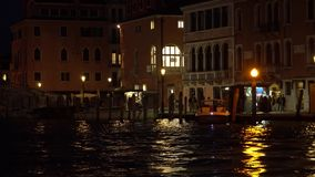 Grand Canal at night. Venice. Italy. Reflection of lanterns in the water. Tourists walk along the promenade. 4K stock video