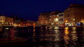 Grand Canal at night. Venice. Italy. Reflection of lanterns in the water. Tourists walk along the promenade. 4K stock video footage