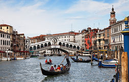 Grand Canal in Venice. Venice, Italy- July 28,2011: Gondola with tourists sailing on Grand Canal in front of the Rialto Bridge in Venice Royalty Free Stock Photo