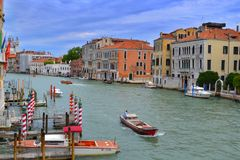 Grand Canal in Venice, colored houses, docks, ships, gondolas and flags. royalty free stock photo