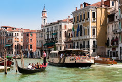 Grand Canal of Venice with gondola and water bus. VENICE, ITALY - JUNE 4: Tourists travelling on gondola and vaporetto water bus on Grand Canal on June 4, 2011 Royalty Free Stock Image