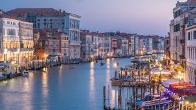 Grand Canal in Venice, Italy day to night timelapse. View on gondolas and city lights from Rialto Bridge. Grand Canal in Venice, Italy day to night transition stock video