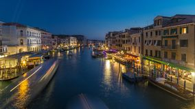 Grand Canal in Venice, Italy day to night timelapse. View on gondolas and city lights from Rialto Bridge. Grand Canal in Venice, Italy day to night transition stock video footage