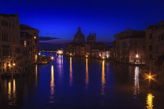 The Grand Canal in Venice, Italy. Just before sunrise as seen from the Accademia Bridge. Salute Church and Customs House in the middle foreground Royalty Free Stock Images