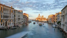 Grand Canal in Venice time lapse with motorboat and clouds passing, Saint Mary of Health at dusk in Italy