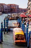Grand Canal, Venice - Travel Italy, Europe. Venice Grand Canal with striped blue and green posts with wooden boats tied. People walking alongside the pier Royalty Free Stock Images