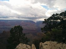 Grand Canyon with  downpour in the distance. Grand Canyon with an  downpour in the distance, and big, white, fluffy clouds Royalty Free Stock Photography