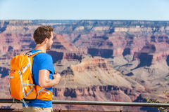 Grand Canyon hiking tourist man with backpack. Bag looking at viewpoint lookout on Grand Canyon, Arizona, USA. People hiking in Grand Canyon enjoying view of stock photo
