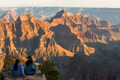 Two women sitting on a rock enjoying the view of the North Rim at Grand Canyo royalty free stock photography