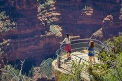 Grand Canyon, o Arizona EUA, JUNHO, 14, 2018: O caminhante de duas mulheres está estando em um penhasco íngreme que recolhe a vis imagem de stock