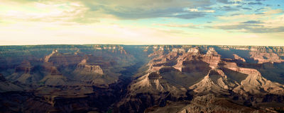 The Grand Canyon. With the path of Colorado River running through it. Sunsetting with blue and yellow skies and clouds. Located in Arizona is one of the Natural Stock Photography