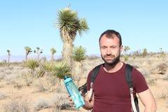Grand Canyon -reis - de gelukkige wandelaar van de mensenberg met rugzak op de rotsachtige droge bergen Stock Fotografie