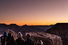 Grand Canyon, RIM Arizona sul Sun que aumentam sobre a garganta, criando cores de surpresa e luzes quando os povos apreciarem o e fotos de stock