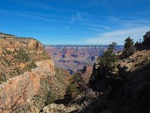 The Grand Canyon Seen From the Trail. A sweeping view of the Grand Canyon on a sunny day taken from one of the hiking trails. Three types of landscape are royalty free stock image