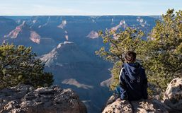 Young Girl sat looking out enjoying the sunset view of the grand canyon. GRAND CANYON, USA - APRIL 15, 2019: Young Girl sat looking out enjoying the sunset view stock photography