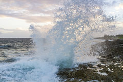 Grand Cayman Blow Hole at Sunset. Spray from the famous Blow Holes on the south coast of Grand Cayman is backlit from the setting sun Royalty Free Stock Photography