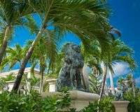 Grand Cayman-Lion Statues. Bronze lion statues on pedestals surrounded by palm trees in the Caribbean, Grand Cayman, Cayman Islands royalty free stock images