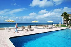 Grand Cayman Resort. The girl walking along the pool of Grand Cayman island resort on Seven Mile Beach (Cayman Islands royalty free stock photos