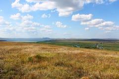 Grand champ près de delta avec des nuages sur le ciel bleu photo stock