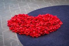 Grand coeur des pétales de rose rouges sur le tapis Cérémonie de mariage Photo stock