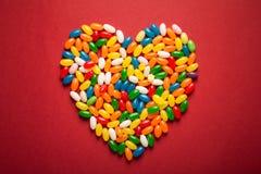 Grand coeur des sucreries colorées sur le fond de papier rouge Image libre de droits