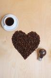 Grand coeur fait en grains de café, tasse de café et ampoule avec des grains de café à l'intérieur sur un fond en bois clair, vue Image stock
