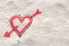 Grand coeur percé par une flèche de l'amour dessinée dans la neige pendant l'hiver Photo libre de droits