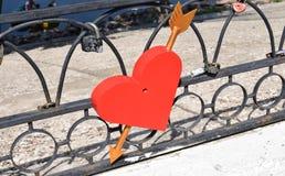 grand coeur rouge de métal percé par une flèche de couleur brune d'or sur une barrière en métal dans la ville un été photos stock