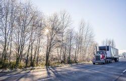 Grand d'installation de jour de cabine d'Américain camion rouge semi transportant la cargaison dans semi couverte la remorque con photographie stock libre de droits