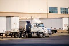 Grand d'installation de jour de cabine camion blanc semi avec de réservoir la remorque semi se tenant dans le dock d'entrepôt ave images stock