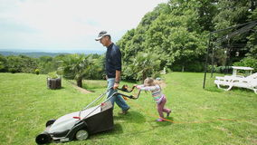 Grand daughter helping mowing the lawn in garden stock footage