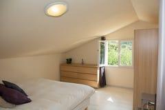 Grand double lit confortable dans la chambre à coucher classique élégante avec des fenêtres photos libres de droits