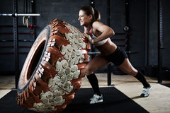 Grand effort. Strong woman flipping heavy tire in gym Royalty Free Stock Photos