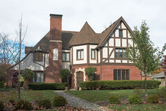Grand English Tudor Home. Large, old English Tudor house in fall with hedge & fireplace chimney Royalty Free Stock Photo