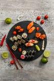 Grand ensemble de sushi, la main qui tient les baguettes, la vue à partir du dessus Photos stock