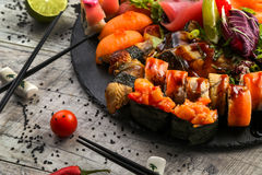 Grand ensemble de sushi, la main qui tient les baguettes, la vue à partir du dessus Photos libres de droits