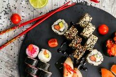 Grand ensemble de sushi, la main qui tient les baguettes, la vue à partir du dessus Photo libre de droits