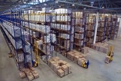Grand entrepôt intérieur avec la haute empilée par fret. Photos stock
