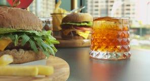 Grand et juteux hamburger de boeuf avec des pommes frites et des cocktails banque de vidéos