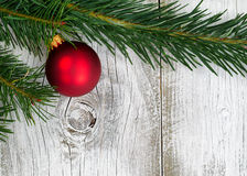 Grand fir branch with singe red ornament on rustic white wooden. Real Grand Fir tree branch with single red ornament on rustic white wooden boards. Christmas Stock Image