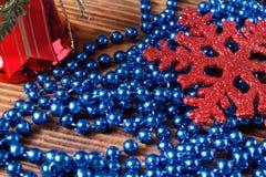 Grand flocon de neige rouge, cloche rouge et perles bleues sur le fond en bois Photos stock