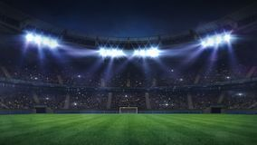 Grand football stadium illuminated by spotlights and empty green grass playground royalty free stock images