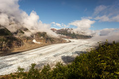 Grand Glacier in Sunlight. A massive glacier flows between rocky and snowy mountains Royalty Free Stock Images
