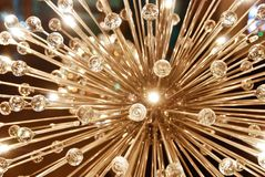 Big electric chandelier made of glass. A grand glass shiny ceiling chandelier in the shape of dandelion Royalty Free Stock Images